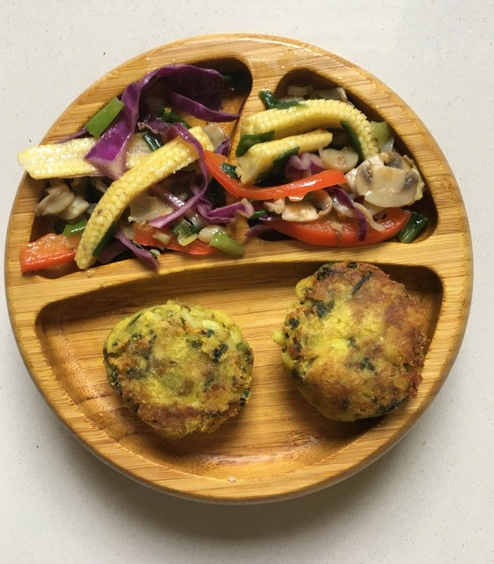 Stir fried veggies laid out on a plate with vegetable patty