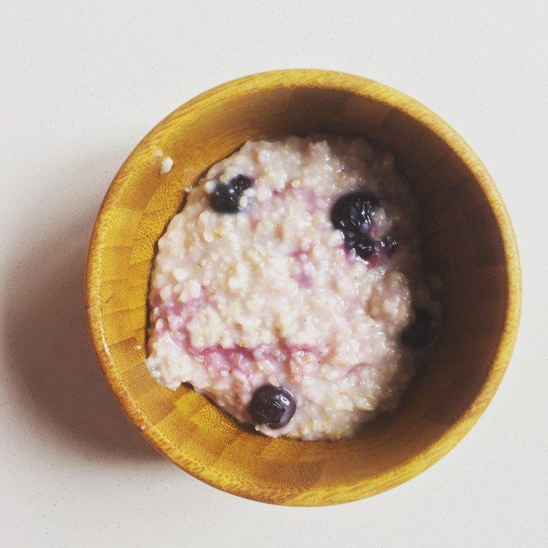 Blueberries sprinkled over a bowl of oats porridge.