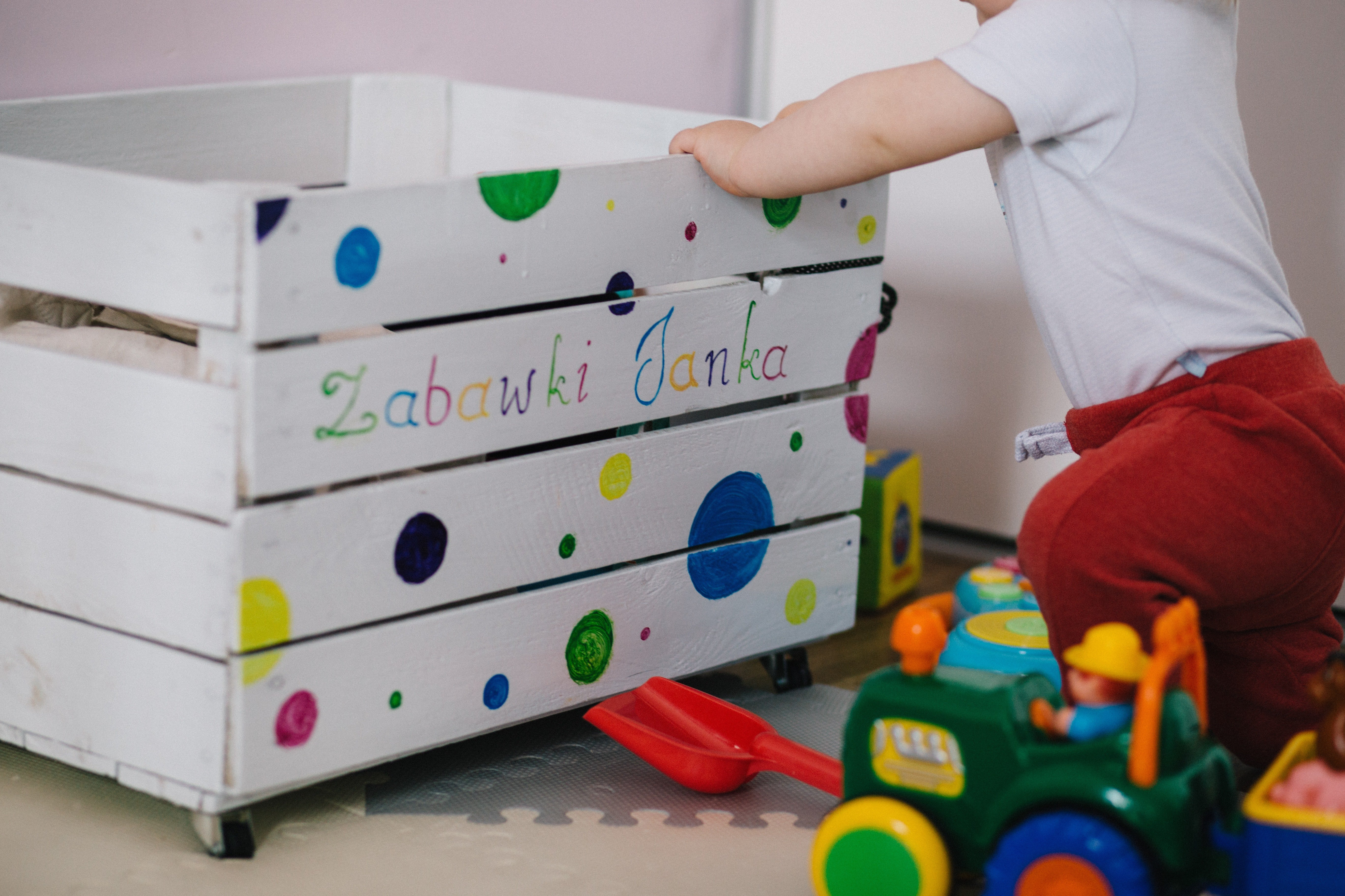 baby playing in nursery with toys